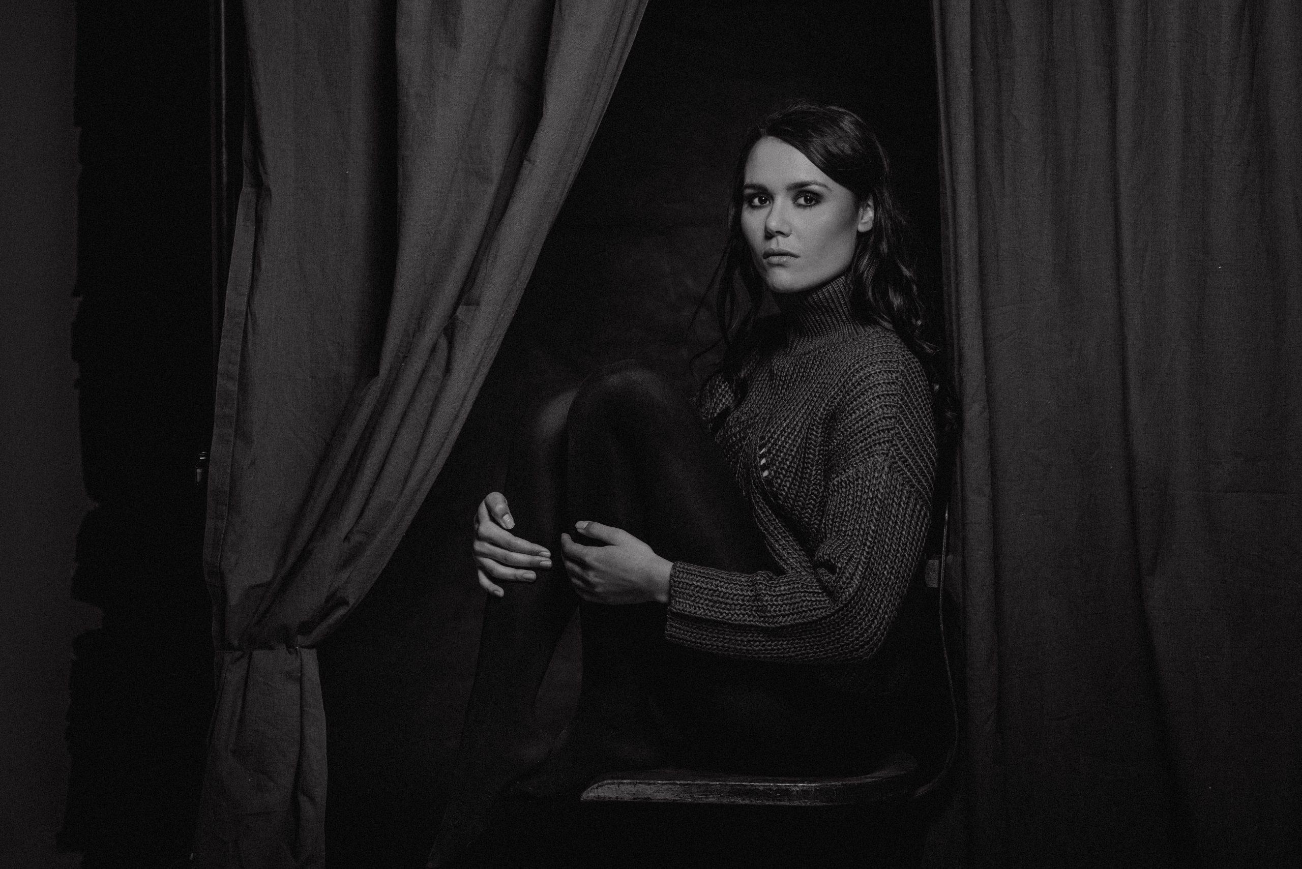 Frau sitzt auf Stuhl hinter Vorhang