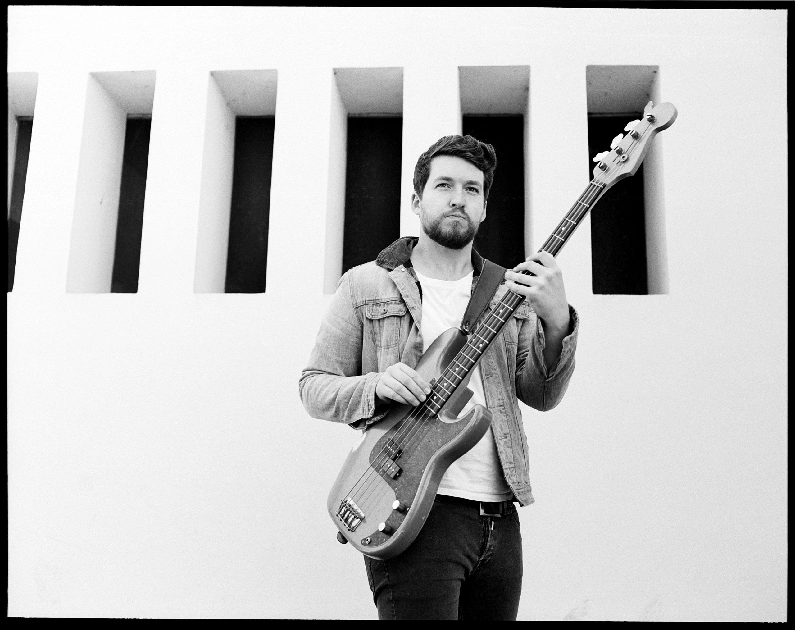 Mann spielt Bass vor weißer Wand