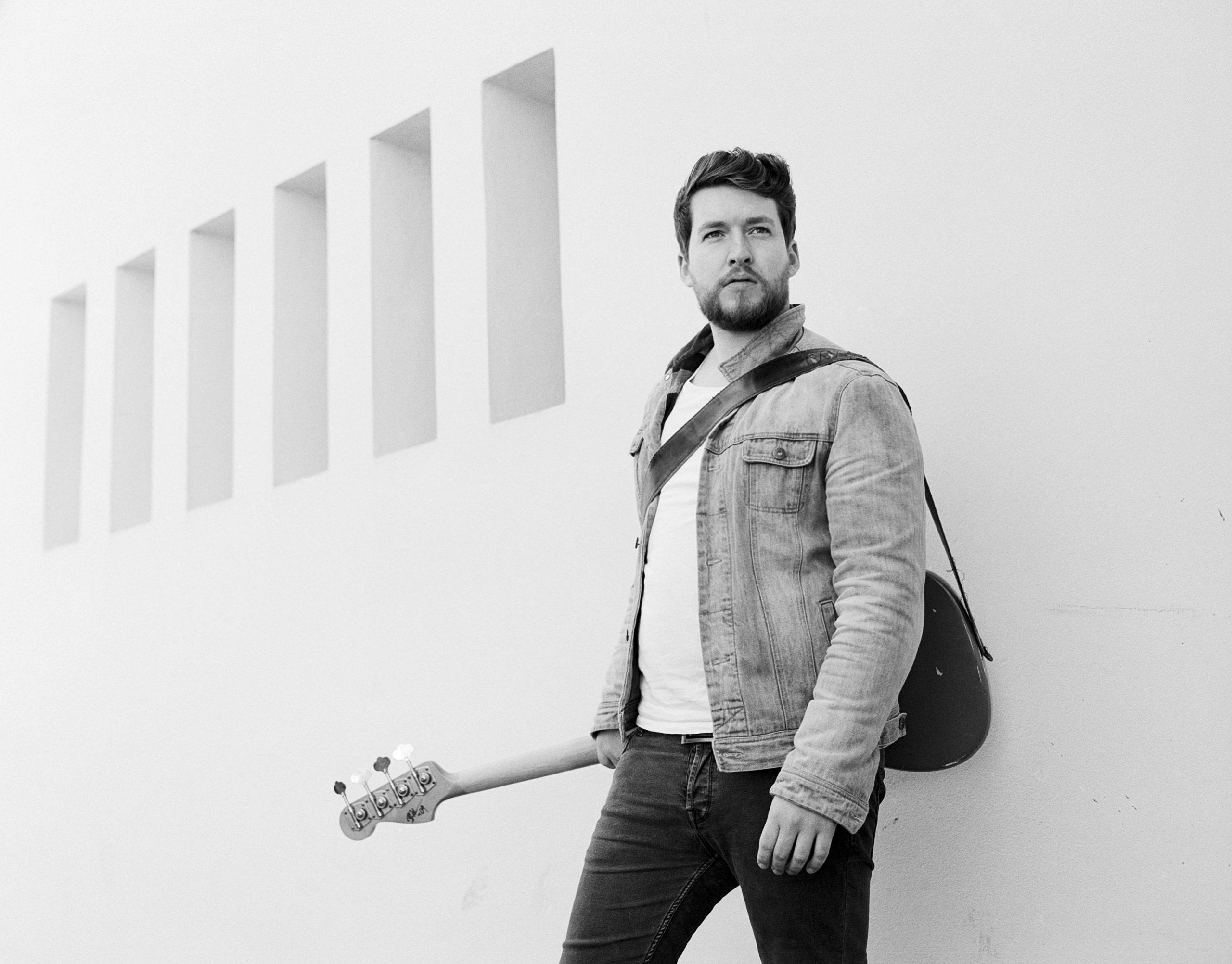 Mann mit Bass Gitarre vor weißer Wand
