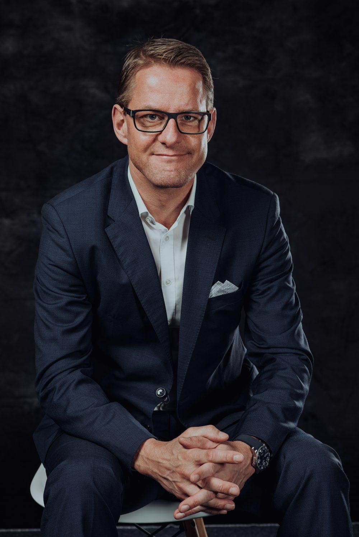 Mann im Anzug mit Brille sitzt auf Stuhl