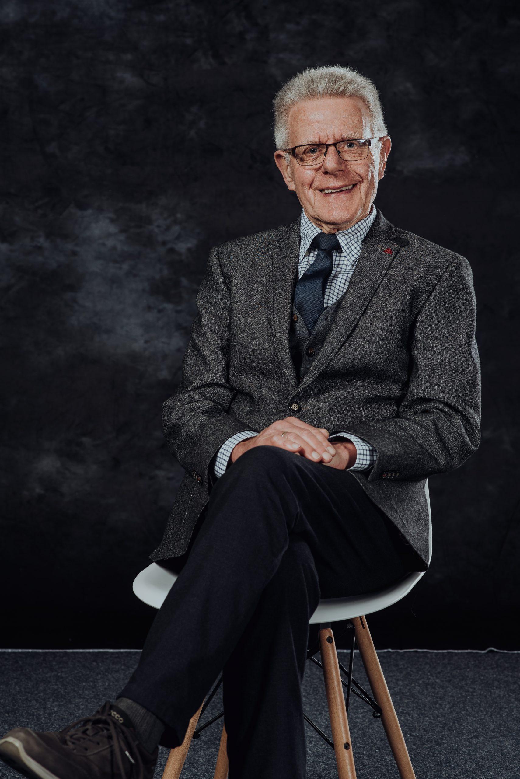 älterer Herr auf Stuhl vor Hintergrund
