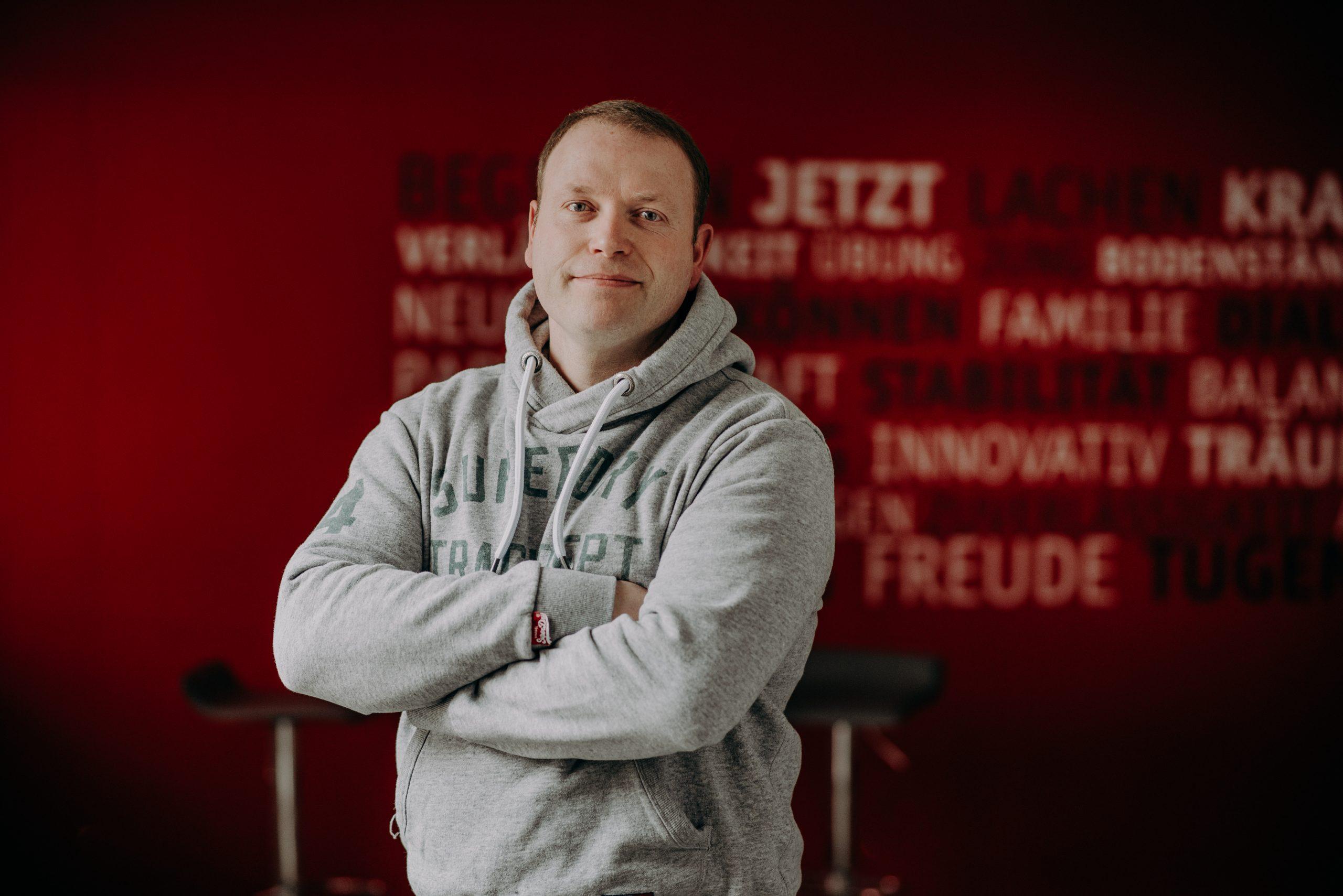 Mann steht mit verschränkten Armen vor roter Wand