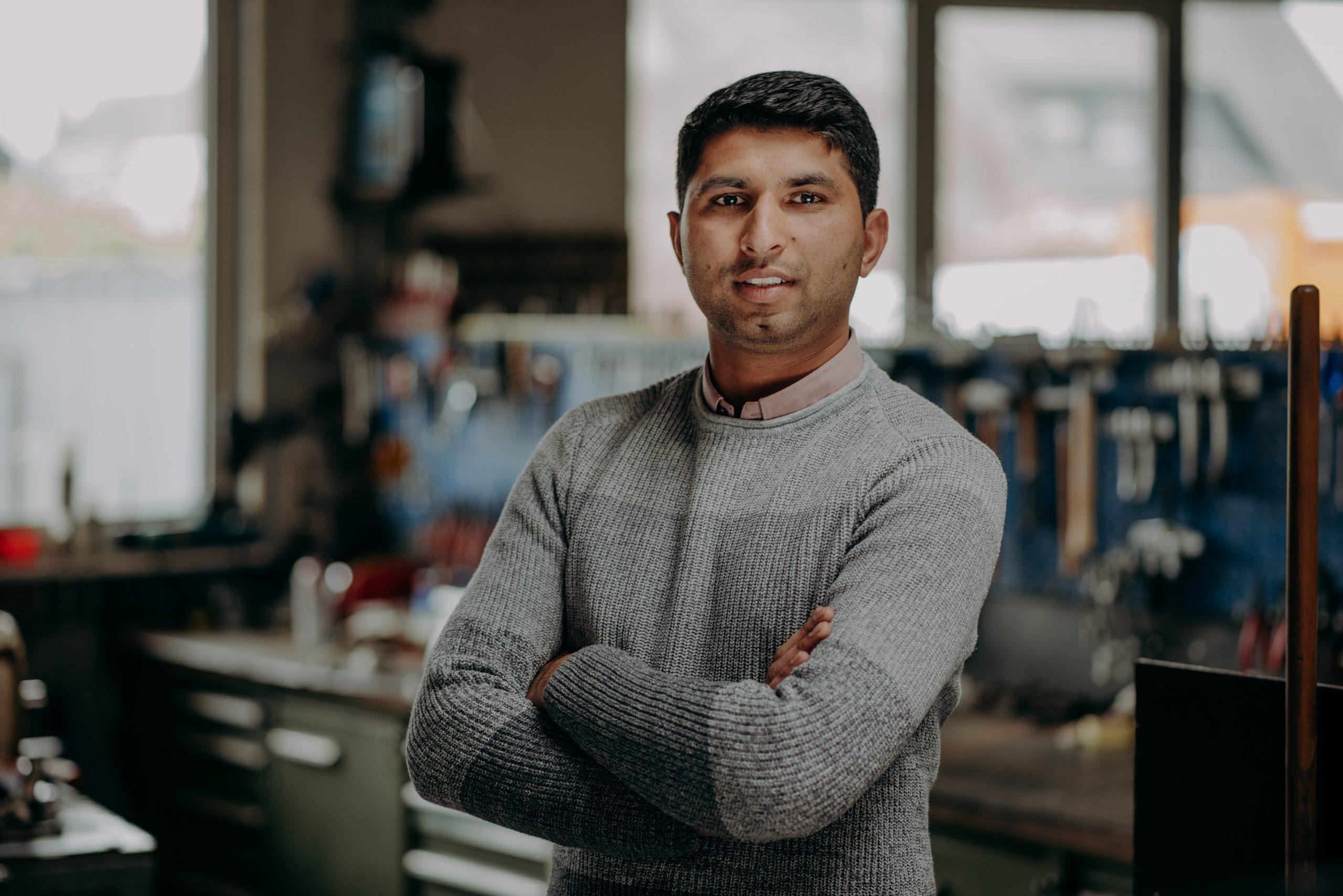 Mann steht Arme verschränkt in einer Werkstatt