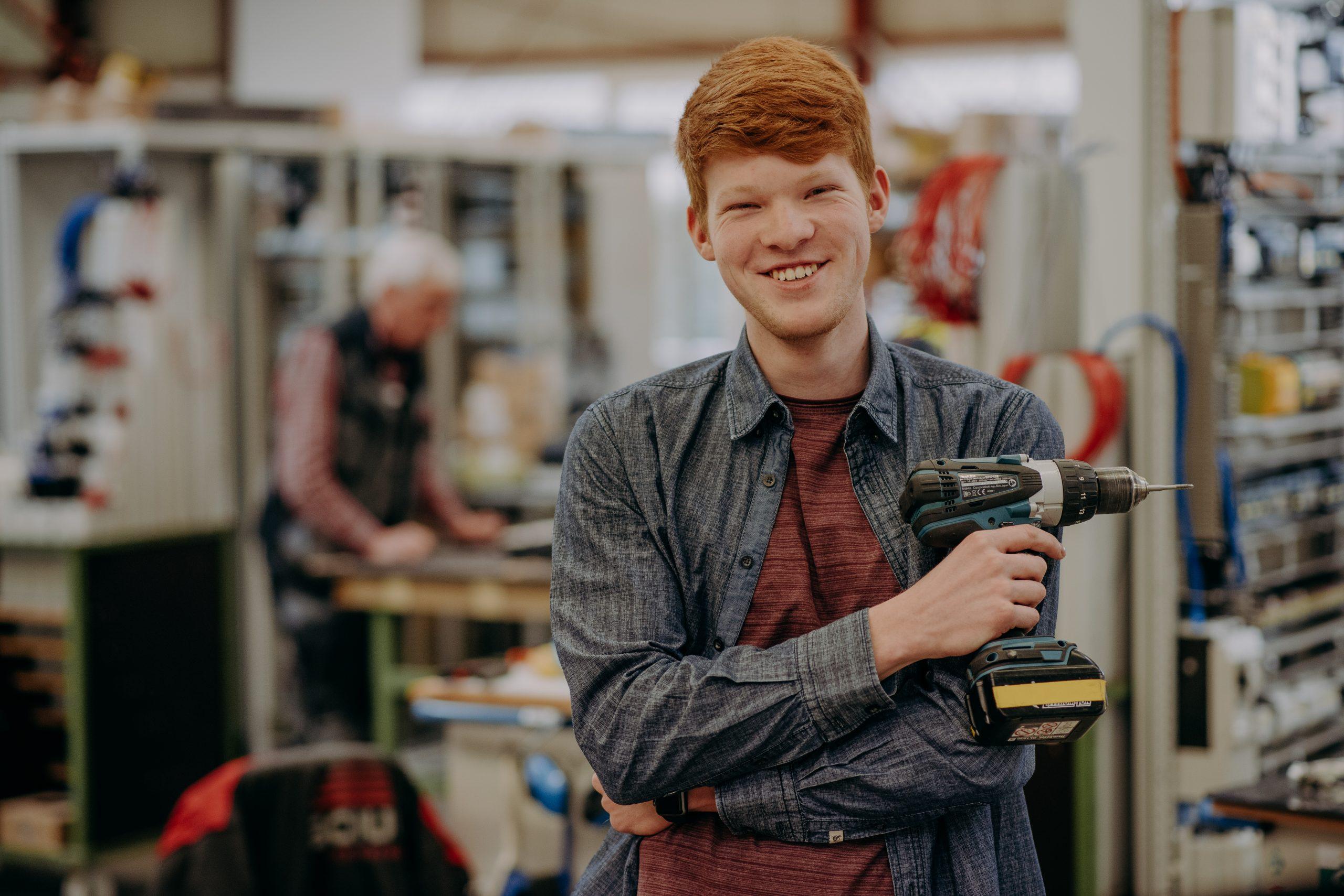 junger Mann mit Akkuschrauber in Werkstatt