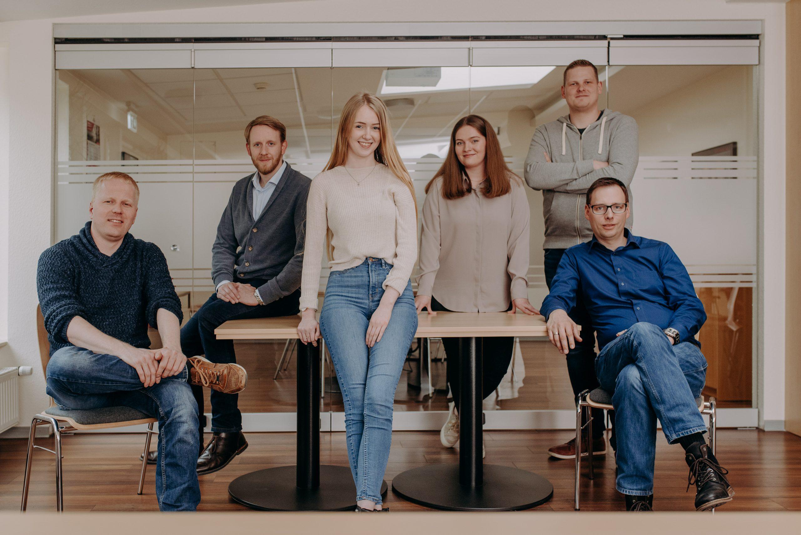 Gruppe aus 6 Menschen sitzt und steht um einen Tisch herum