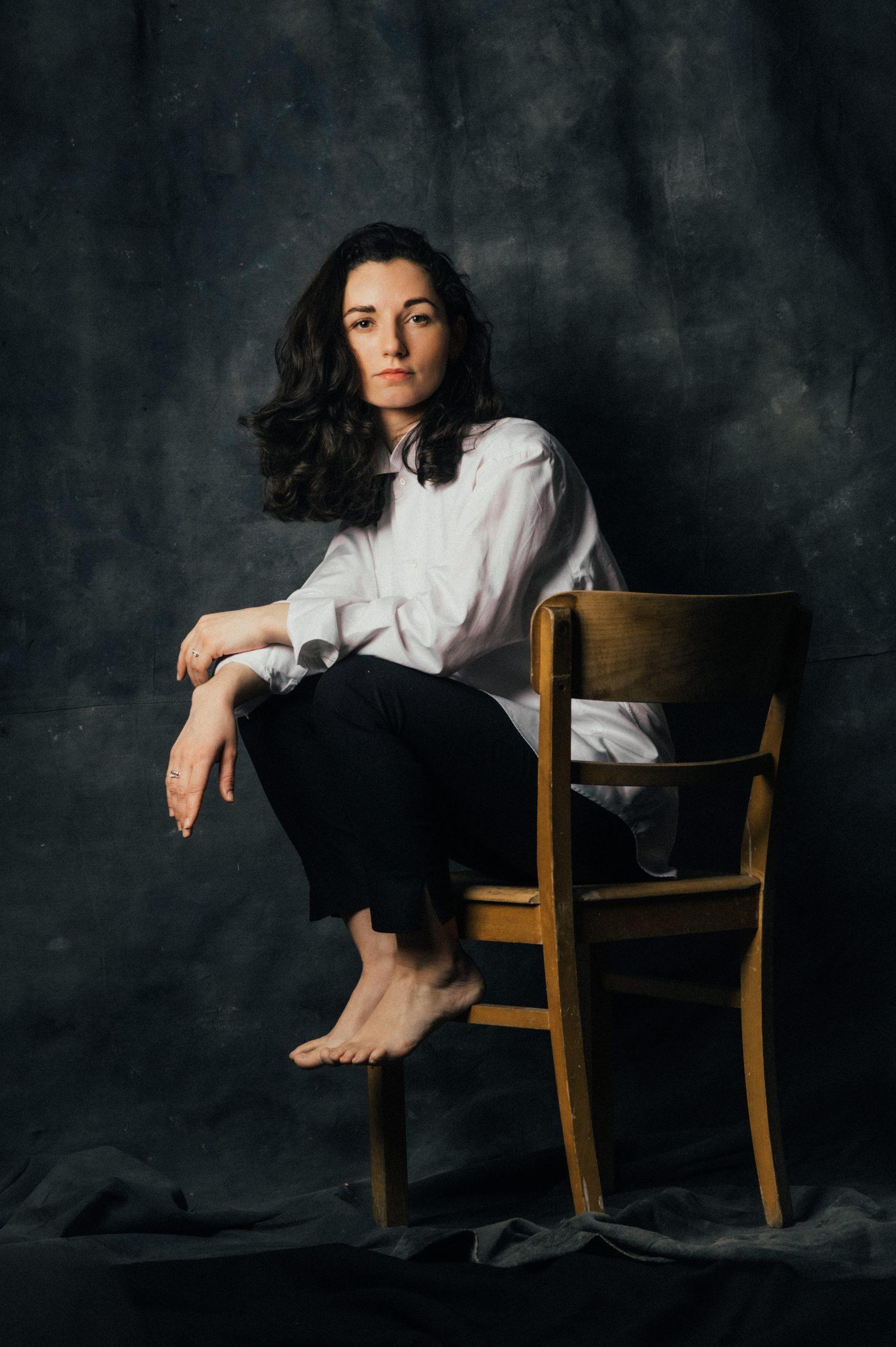 Frau sitzt auf Holzstuhl