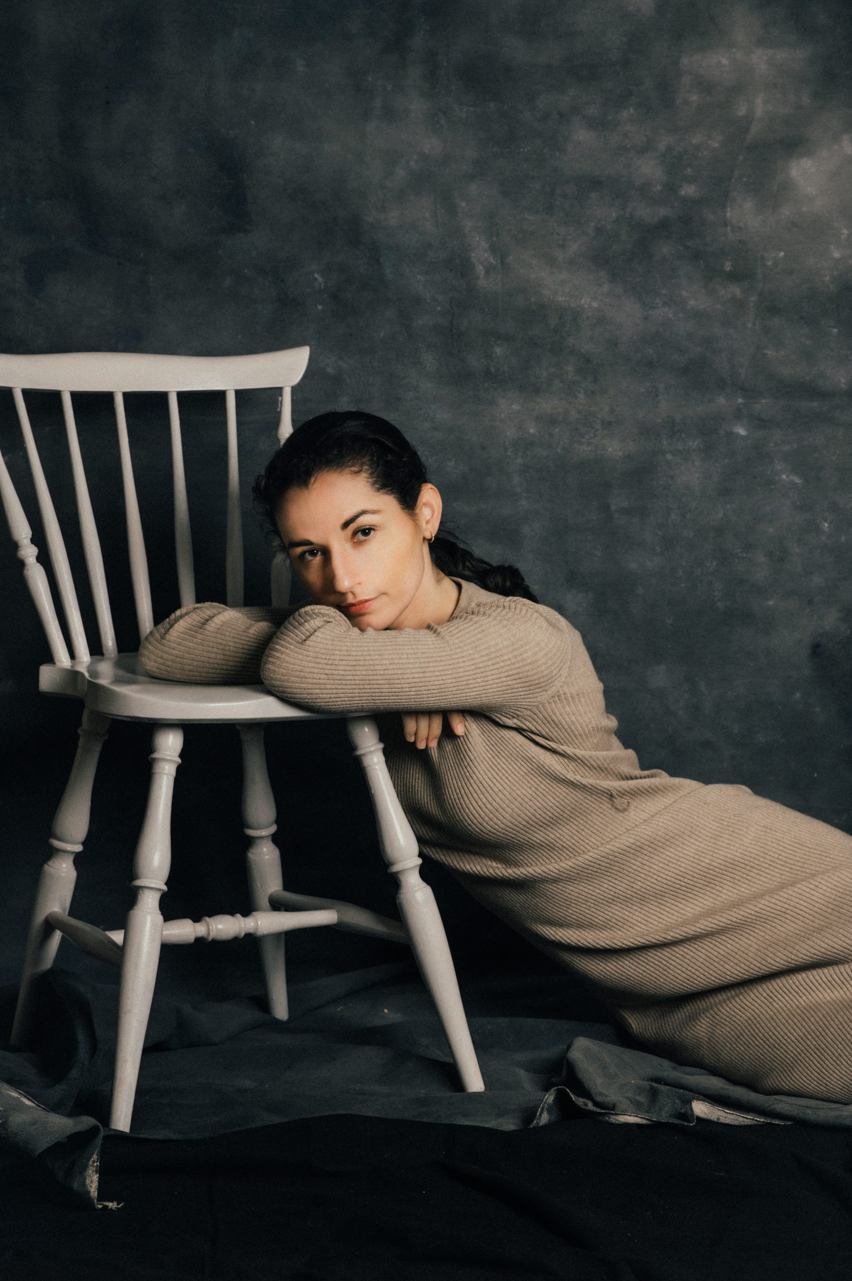 Frau liegt neben weißem Stuhl