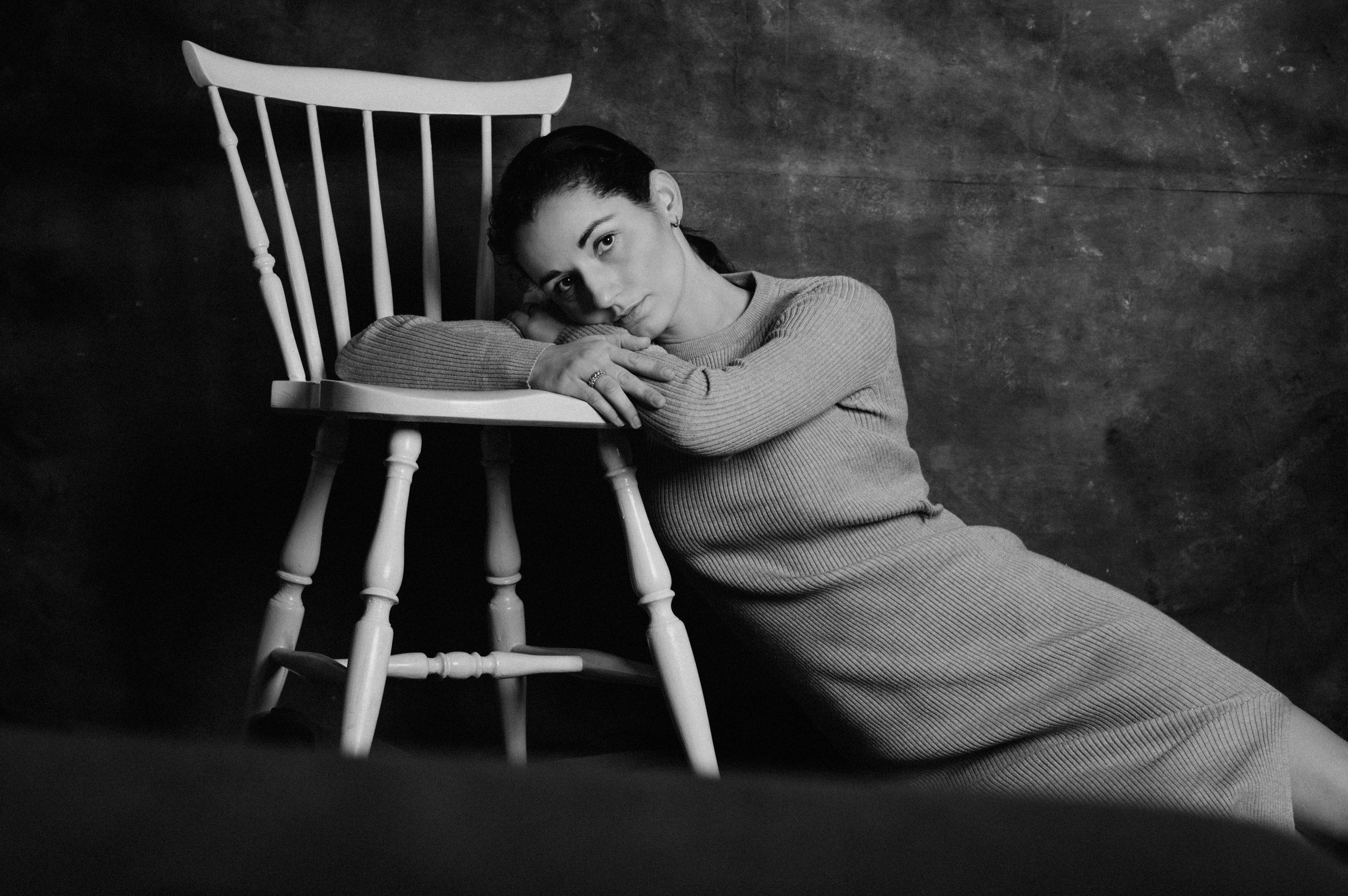Frau mit Ellenbogen auf Stuhl aufgestützt