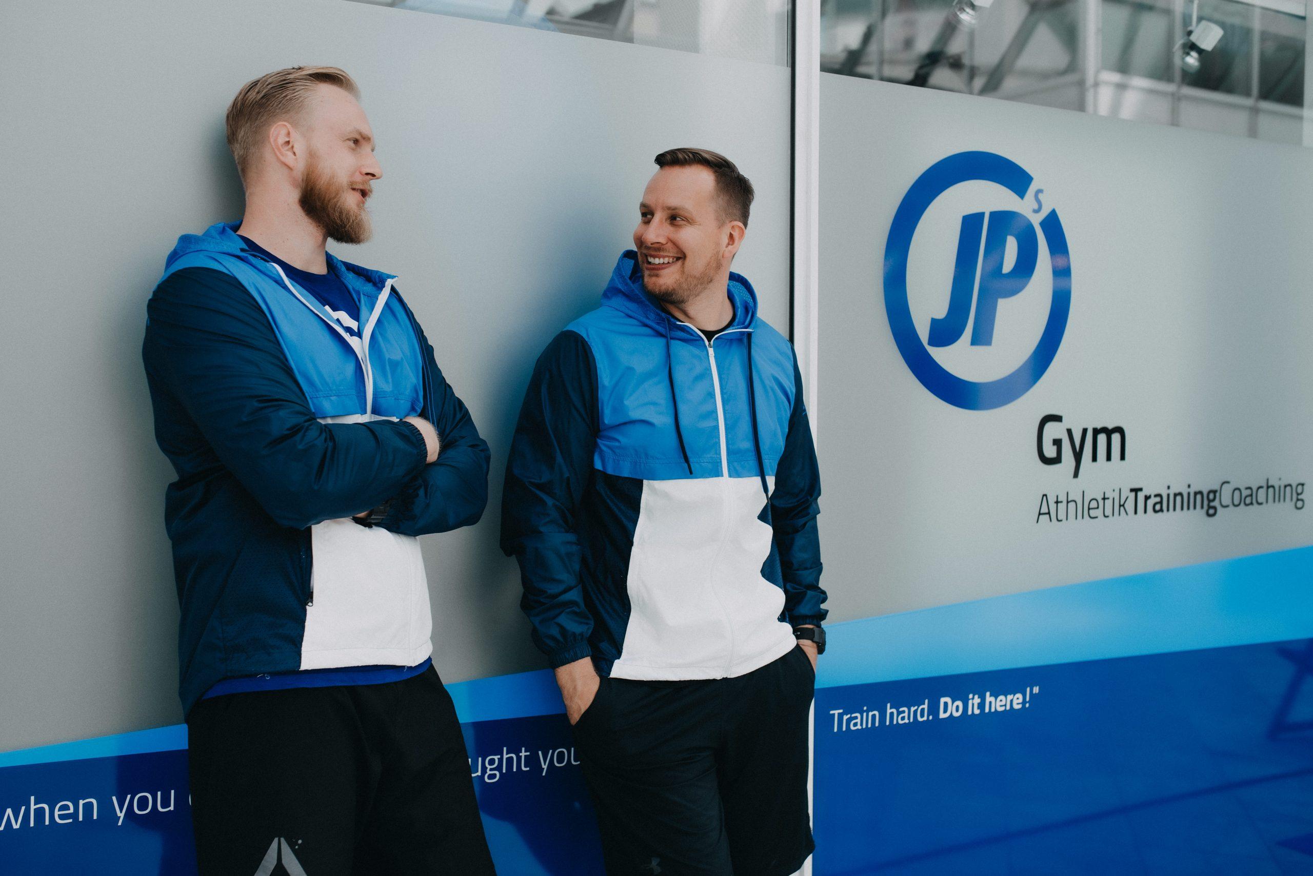 Zwei Männer lachend vor Fitnesstudio