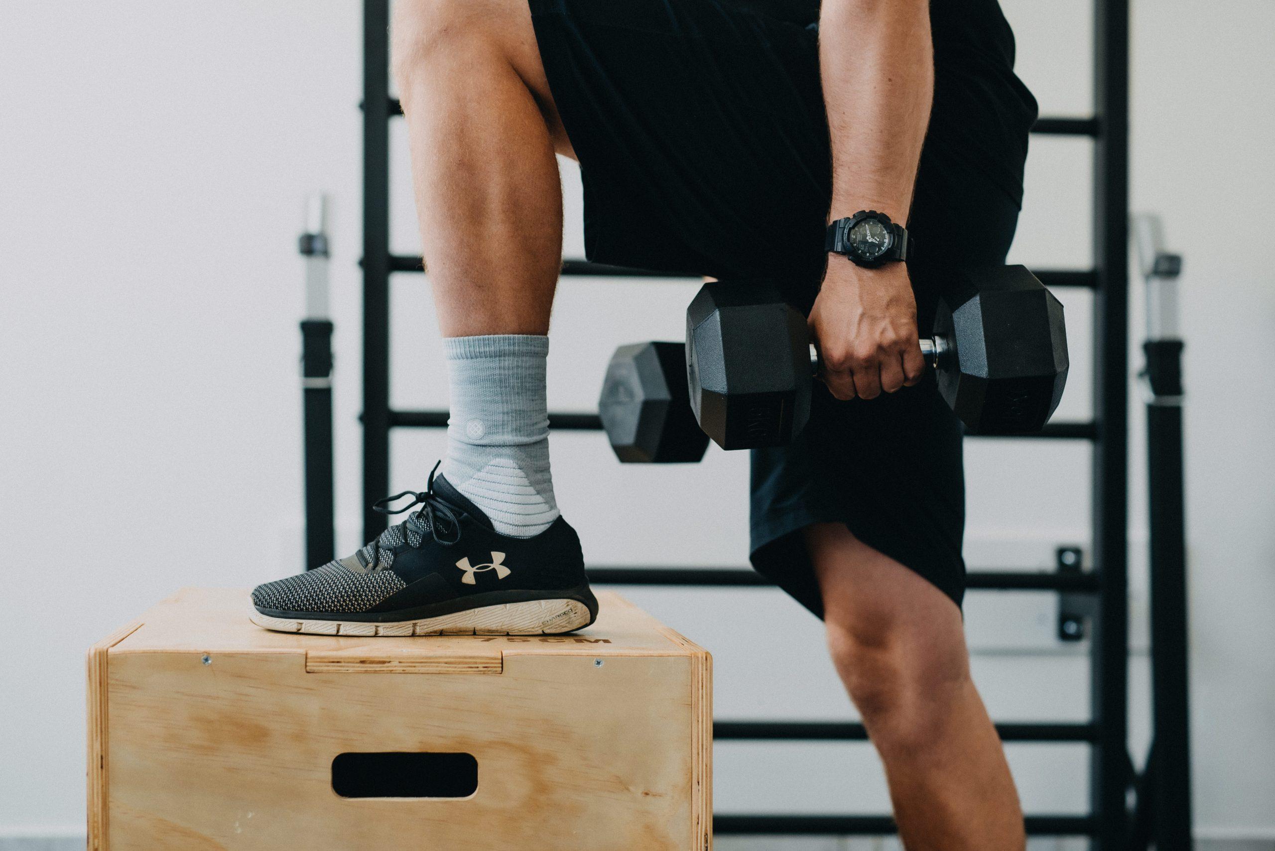 Sportler mit Hanteln und Bein auf Kiste