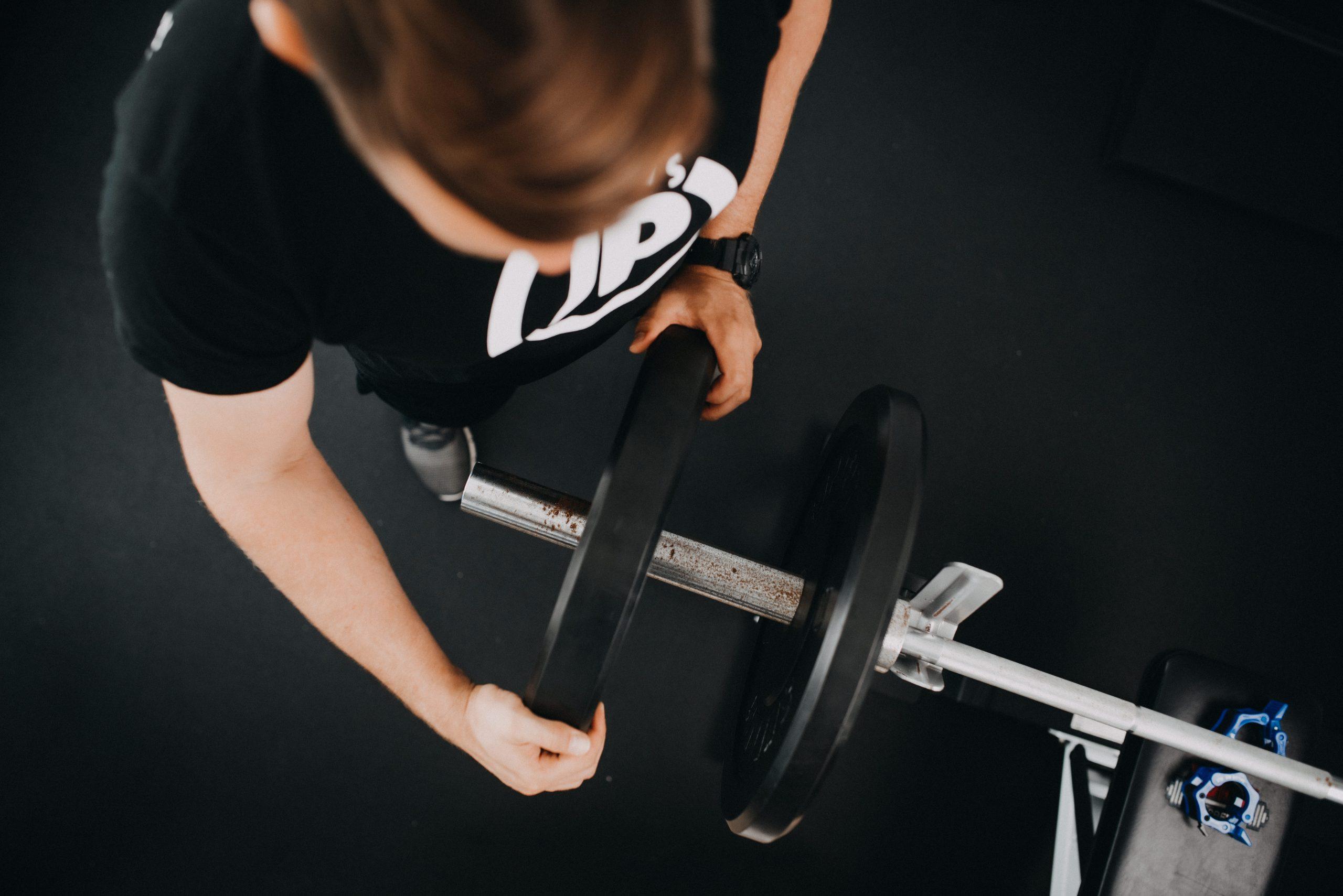 Mann schiebt Gewichte auf Hantel
