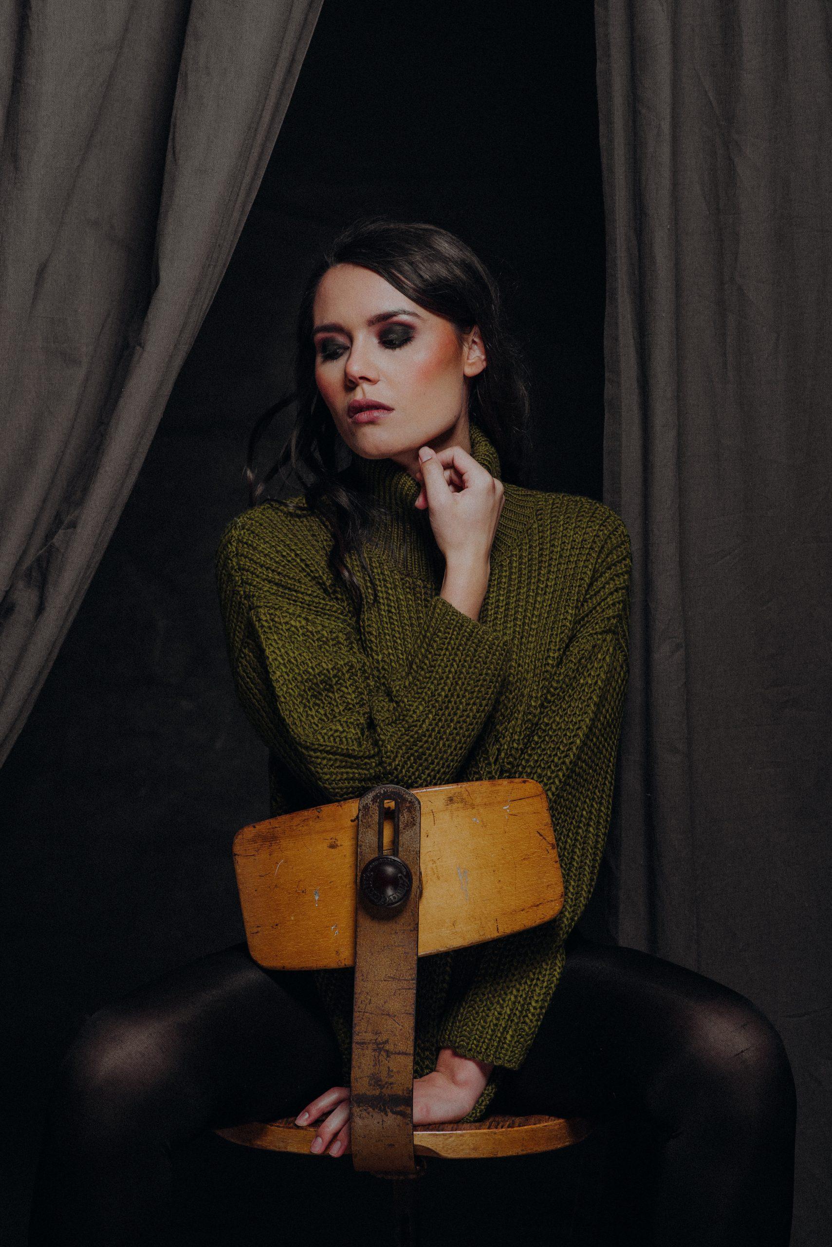 Frau sitzt falsch herum auf Holzstuhl