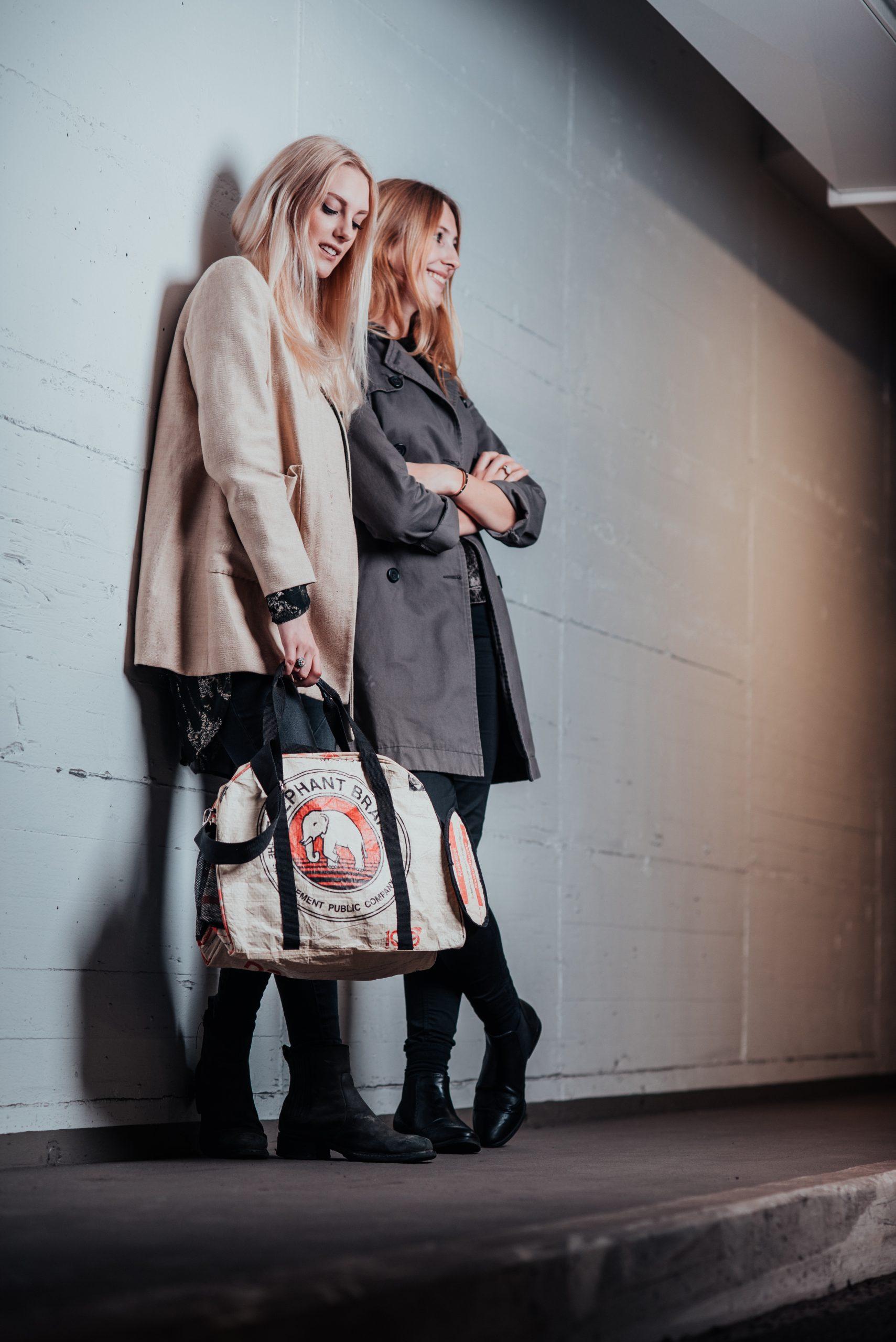 Zwei junge Frauen lehnen an Parkhauswand
