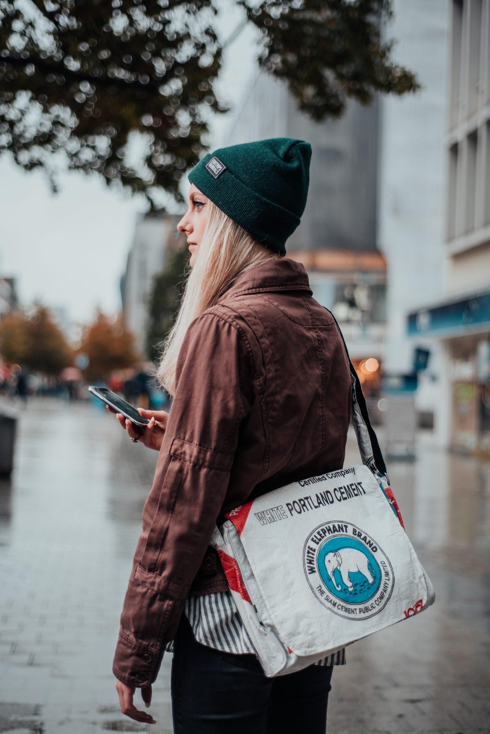 Frau mit Mütze und Handy in der Hand