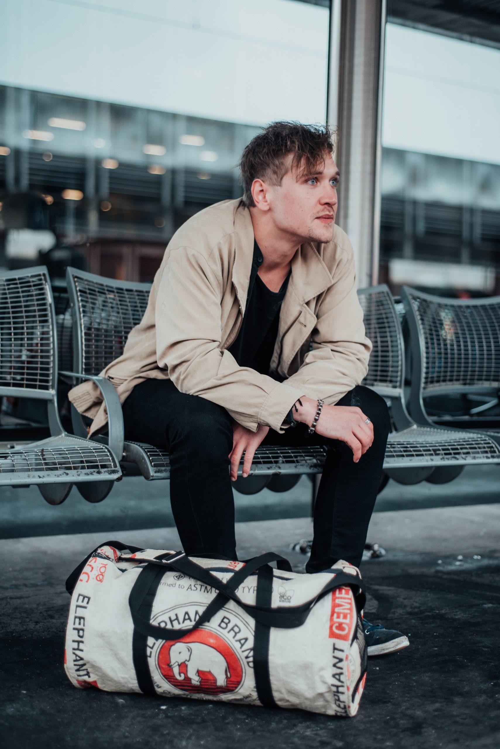 Mann sitzt mit Reisetasche am Bahnsteig