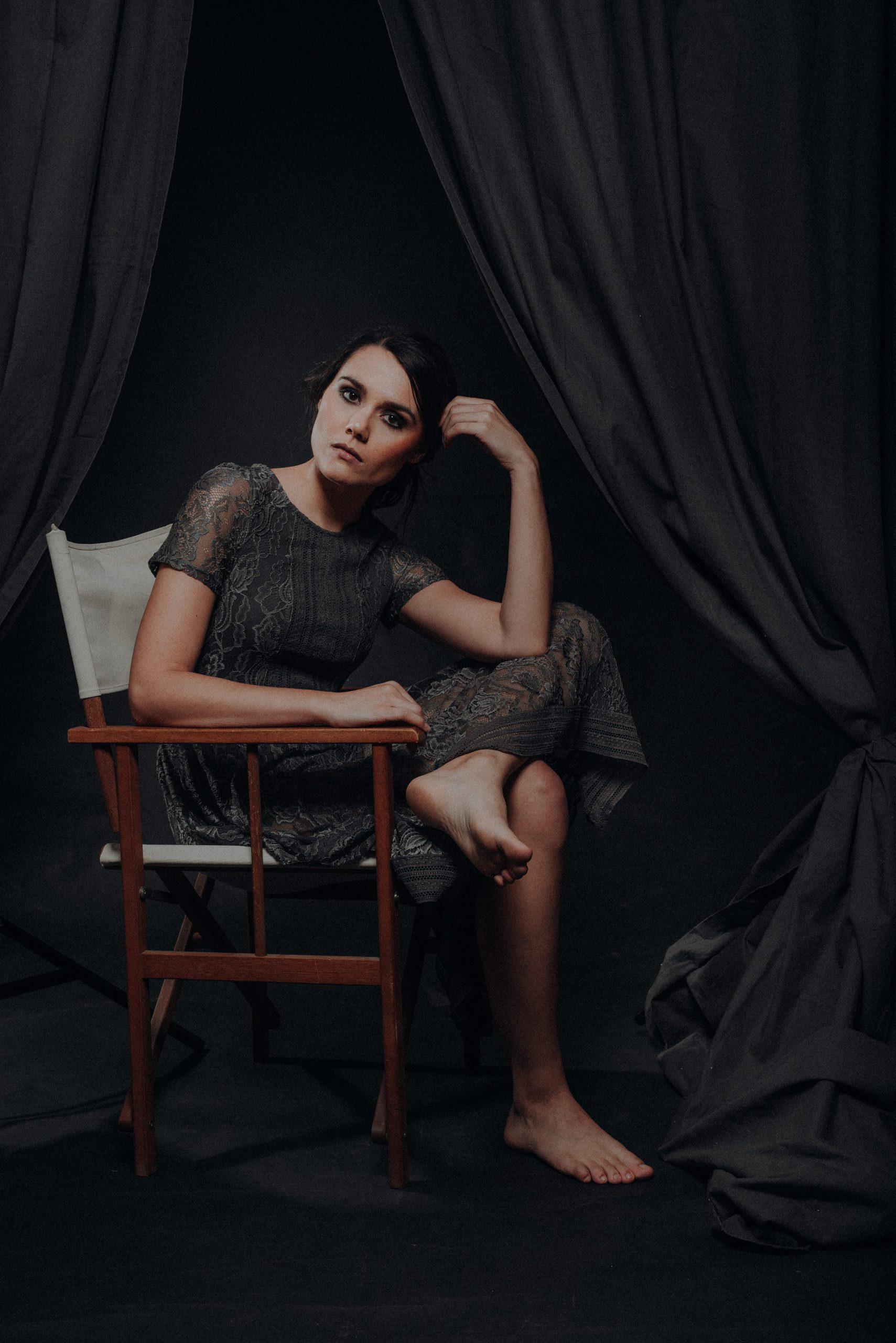 Frau in Kleid auf Holzstzuhl