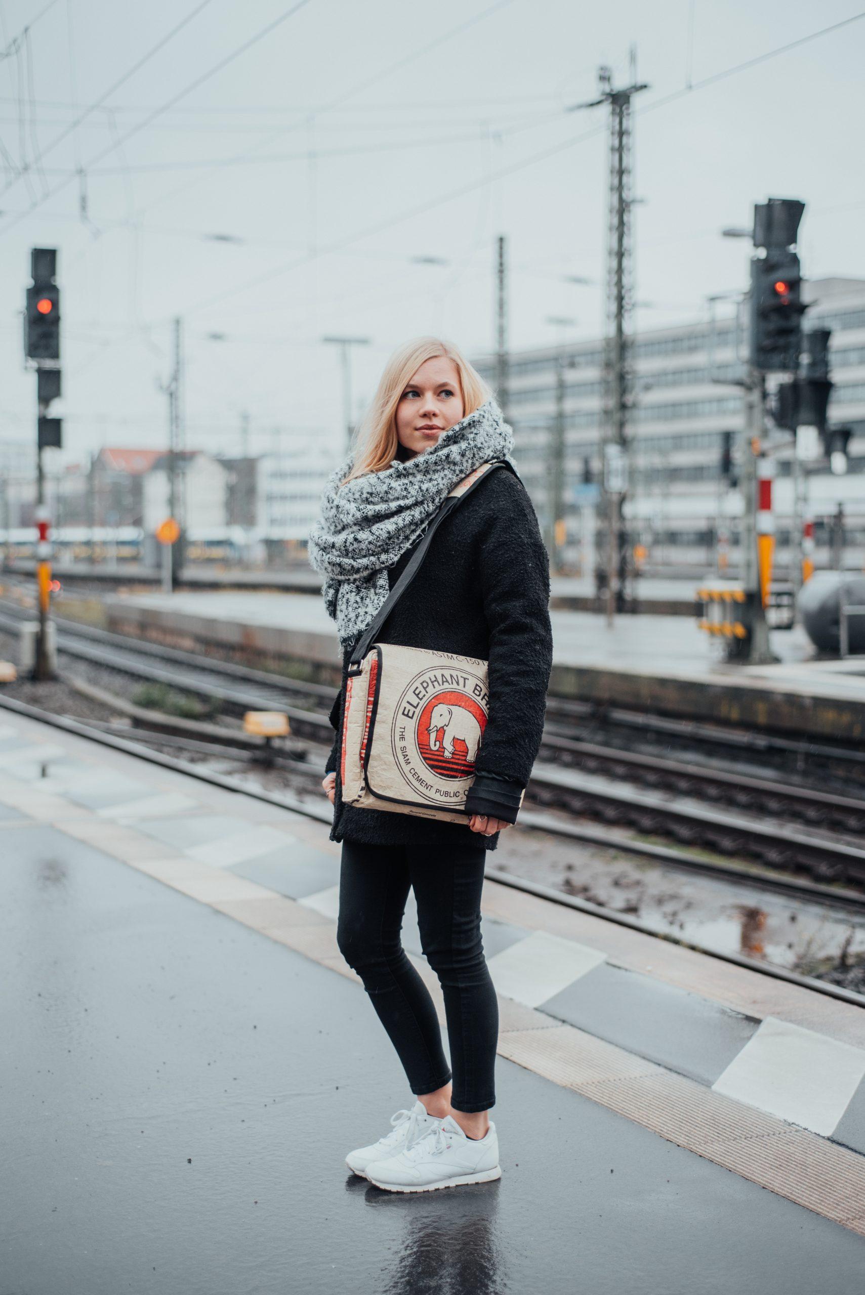 Frau mit Tasche auf Bahnsteig