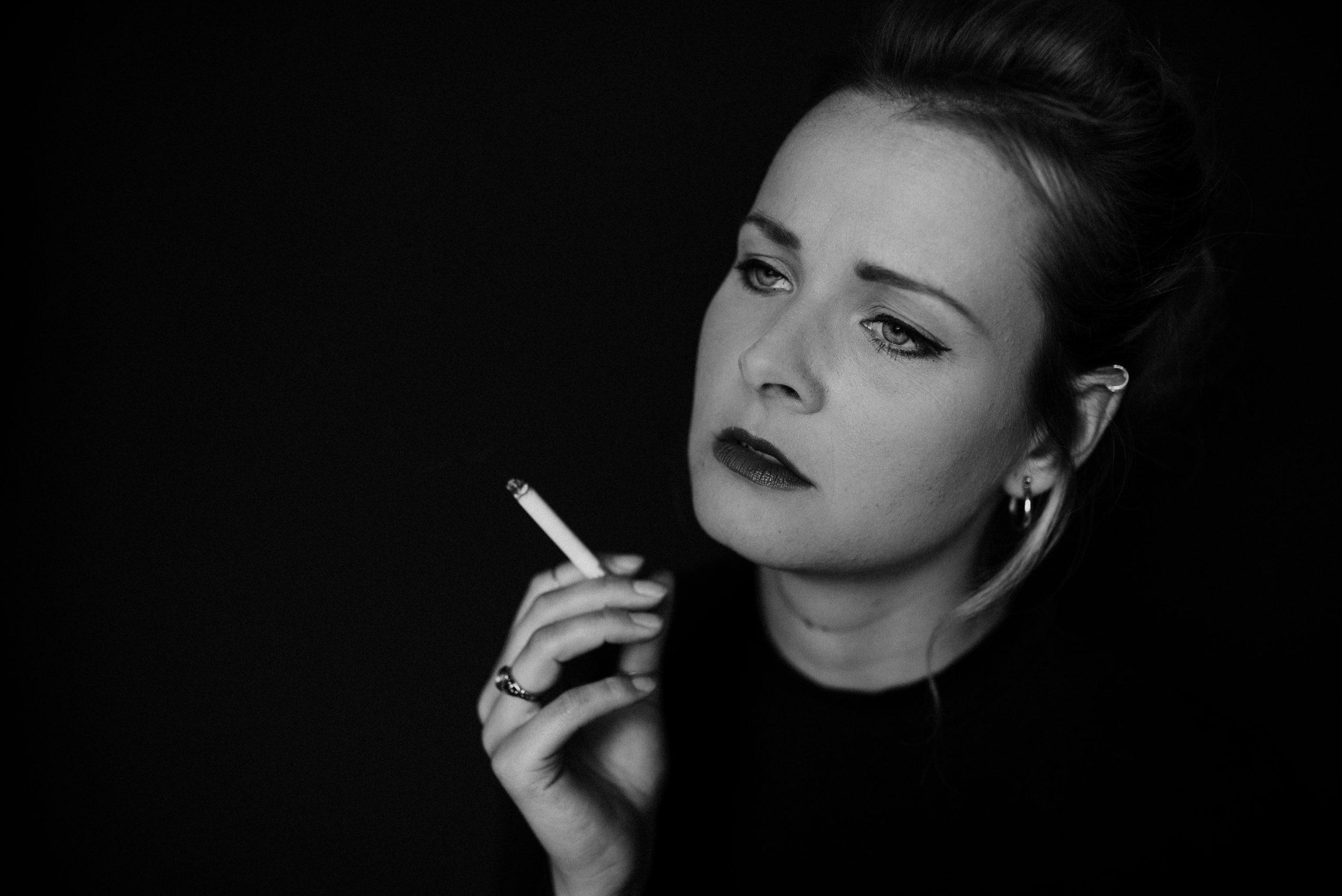 Frau mit Zigarette blickt zur Seite