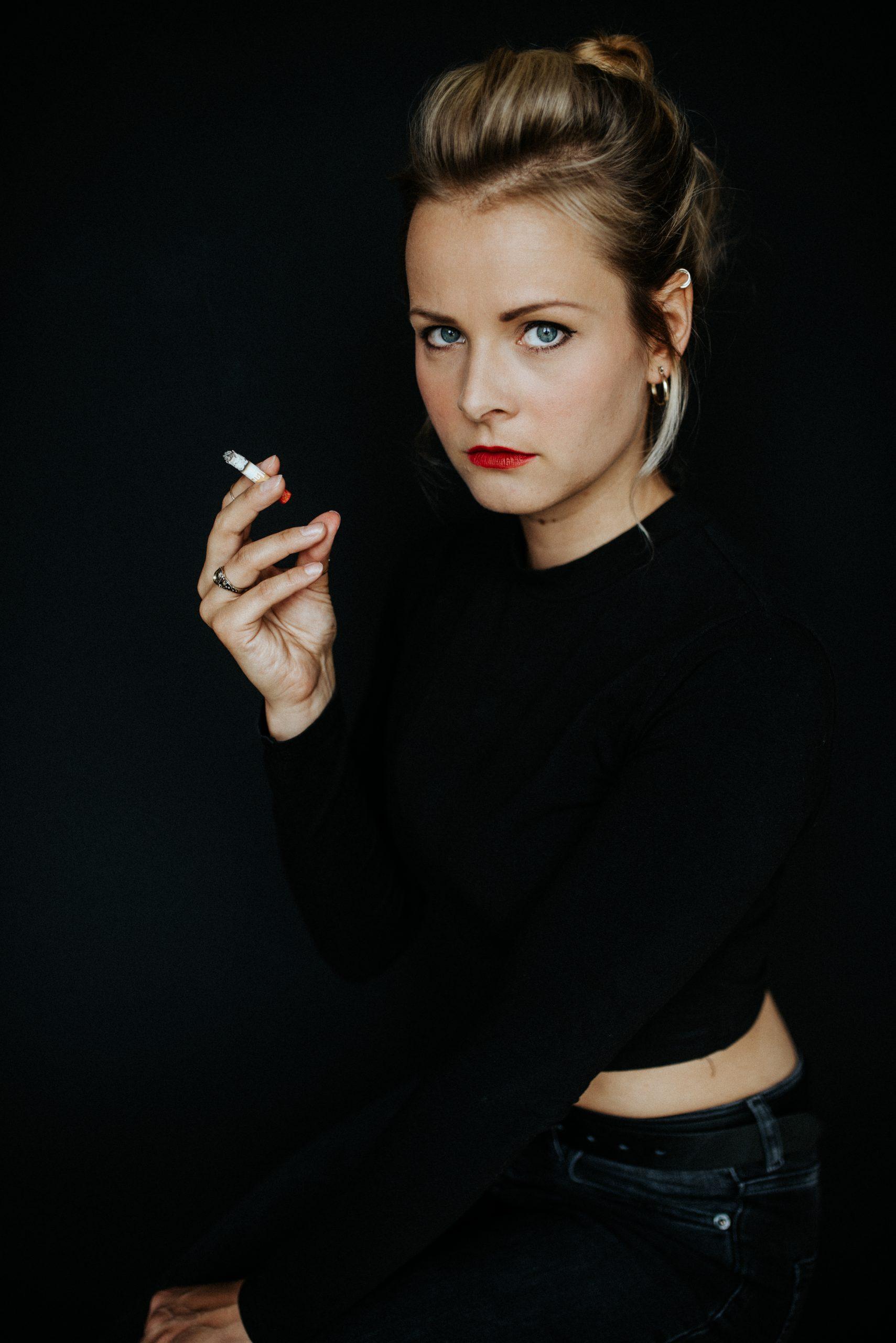 Frau mit Zigarette schaut ernst in Kamera