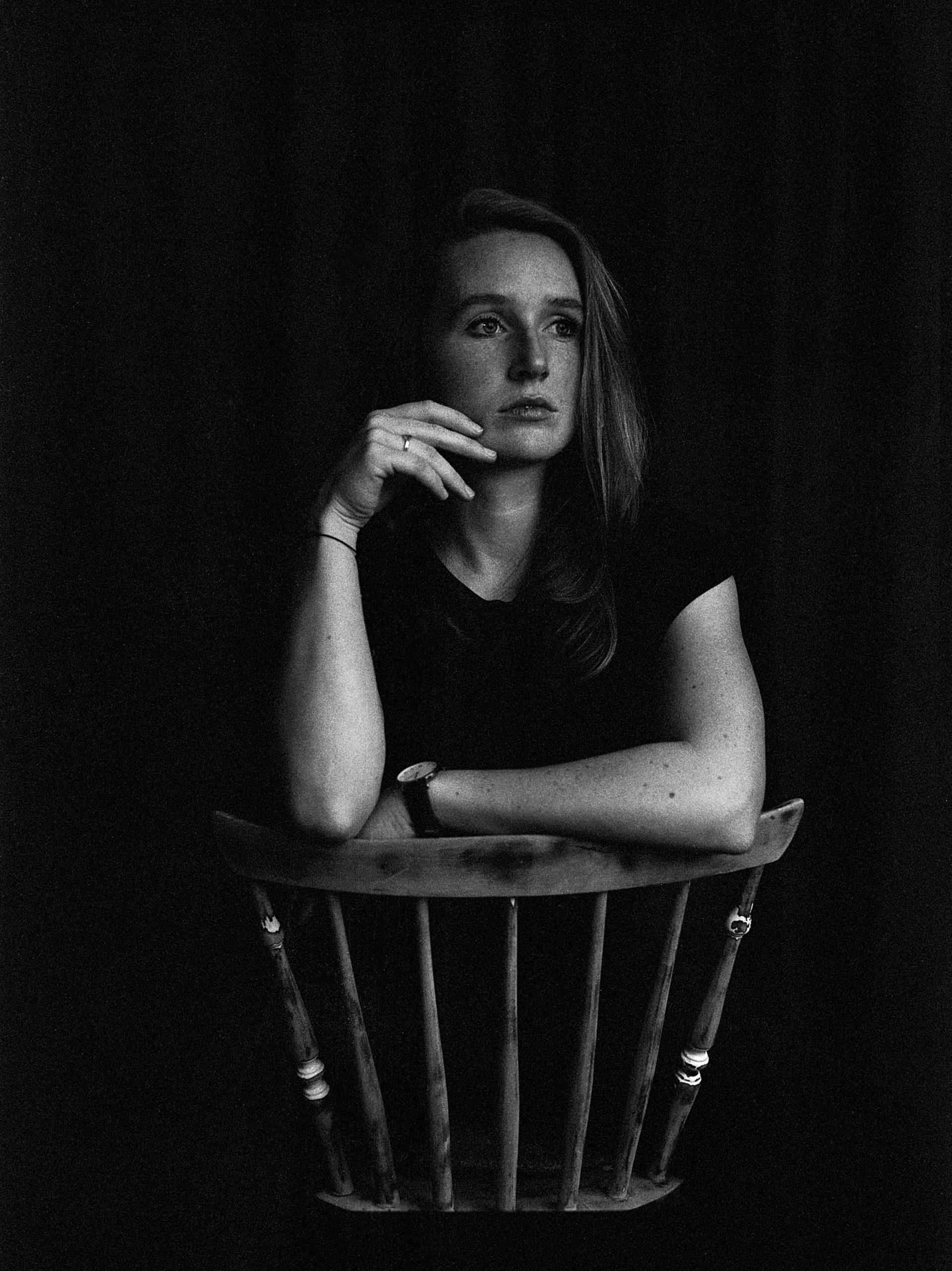 Frau sitzt verkehrt herum auf Stuhl