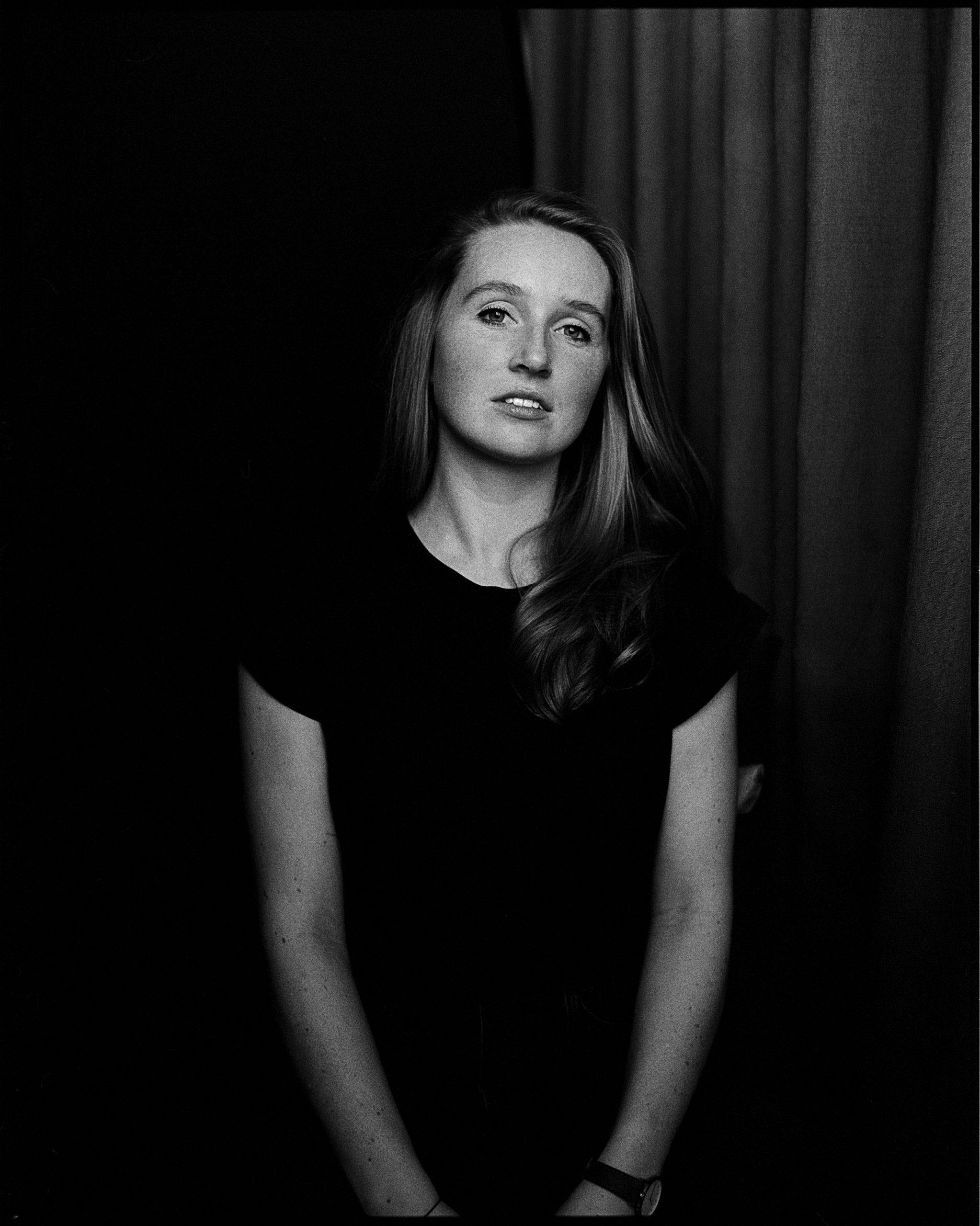 junge Frau sitzend vor dunklem Hintergrund