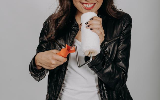 junge Frau nutzt Malerrolle als Mikrofon