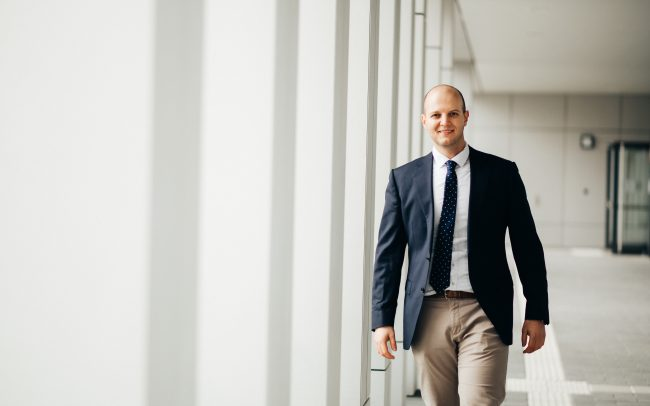 Mann im Anzug läuft vor einem Gebäude